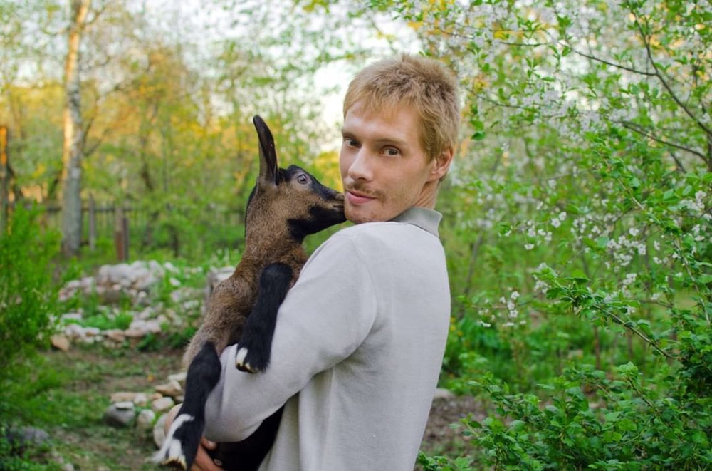 guy with a little goat in his hands in the spring garden